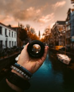 what are you looking for how to create the life you want woman's hand holding lens focused on water town