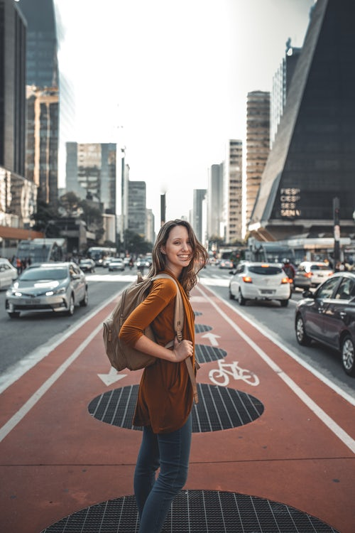 Young woman with backpack, ready to travel, standing in city street
