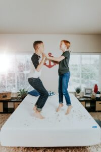 family mental health a boy and girl tween jumping on a bed