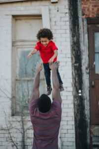 family mental health covid black dad tossing happy child into the air