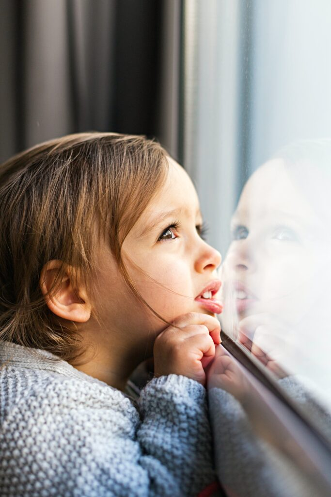 family mental health covid little girl looking out window