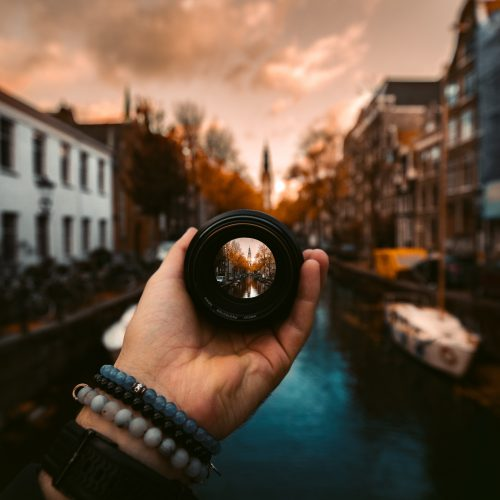 woman's hand holding lens focused on water town