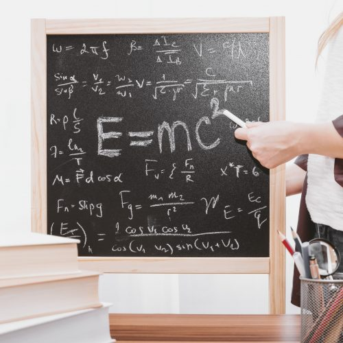 woman pointing to E=mc squared on small chalkboard